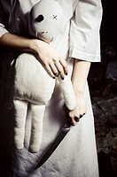 Horror style shot: a moppet doll and knife in someone's hands