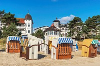 Beach chairs at the Baltic Sea beach, Baltic resort Binz. Behind the beach is the beach promenade with houses in the style of resort architecture, Bal...