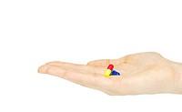 finger holds pill isolated on white