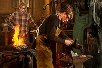 Flames rise as modern day amateur blacksmiths stoke their traditional coal forges and use a trip hammer on red-hot iron at an 1890´s-era blacksmith sh...
