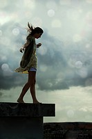 Young woman walking on a rooftop with her arms outstretched