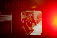 USA, New York State , Paramedic checking heart rate of senior man in ambulance