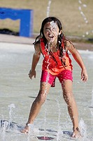 A little girl playing in the water at a water park.