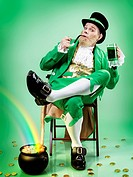 Leprechaun wearing a green suit, holding a smoking pipe and a mug of green beer, rainbow coming from a pot full of gold, conceptual St. Patrick's day ...