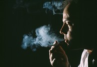 Man exhaling smoke from cigarette.