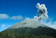 Smoke rising from the volcano as it erupts above the tree lined base with dust surrounding the summit