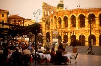 Piazza Bra. Busy cafe with people eating and drinking at outside tables in front of the Arena.