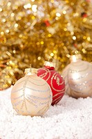 Red and gold Christmas baubles on golden background