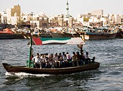 Abra water taxi with commuters crossing the Creek Souk market behind.