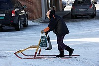 old woman carrying shopping around town using a kicksled spark kirkenes finnmark norway europe.