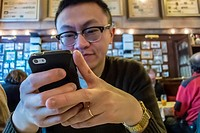 "Berlin, Germany, Chinese Tourist Inside, German Cusine Restaurant, """"Joseph Roth Diele"""", Sending Text Message Holding Iphone, Smart Phone at Table"