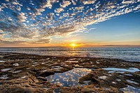 The Sun setting over the Pacific Ocean viewed from the Ocean Beach tidepool area. San Diego, California, United States.