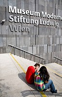 Neubau District. Young student couple sitting on the steps of the Museum of Modern Art Museum Moderner Kunst Stiftung Ludwig Wien or MUMOK.
