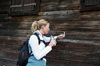 Woman using cell phone and drinking from bottle