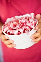 Child holding bowl with spiral sweets