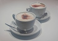 Two cups of capuccino soft focus on white