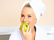 pretty woman eating a green apple