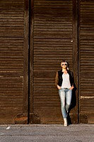 Young woman with sunglasses leaning against wooden gate