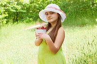Child girl with bucket of strawberries