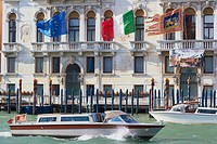 Water taxis on the grand canal passing Palazzo Ferro Fini, Venice, Veneto, Italy, Europe.