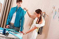 Female fashion designer measuring jacket on model