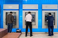 Three Men in a Bank Lobby, Using the ATM Machines.