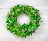 Seasonal green leaf wreath on rustic white wood