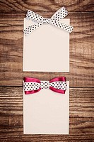 two blank paper sheets with colorful bows on wooden background