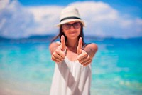 Young beautiful woman showing thumbs up on the beach