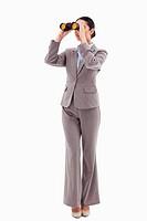 Portrait of a brunette businesswoman looking through binoculars