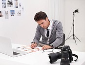 Shot of a young photographer sitting at his desk editing images
