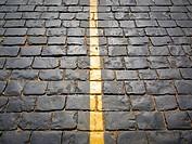 Yellow stripe on a sett paved road