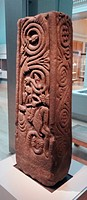 Anglo-Saxon stone cross-shaft fragment from the shaft of a larga, free-standing stone cross, carved with Christian imagery. The swirling vines evoke t...