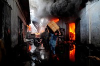 (150624) -- KARACHI, June 24, 2015 () -- A man removes belongings from a warehouse after a fire erupts in southern Pakistani port city of Karachi, Jun...