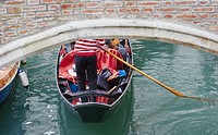 Gondolier in traditional red and white striped top rowing a gondola under a bridge, Castello, Venice, Veneto, Italy, Europe.
