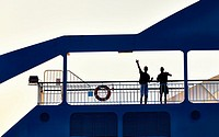 Two young men greeting from a ferryboat. Denia. Alicante. Valencia Community. Spain.