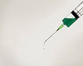 Syringe with green liquid.