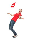 Happy young woman throwing Santa hat