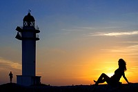 Sunset. Pretty woman backlight in Es Cap de Barbaria lighthouse, in Formentera, Balears Islands. Spain. Barbaria cape formentera lighthouse road.
