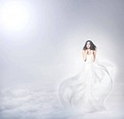 Young and beautiful angel woman in blowing dress over the heaven background