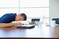 Caucasian businessman sleeping at conference table