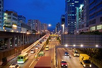 busy motorway and apartments at dusk in Kowloon Bay, China.