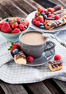 Cup of coffee and chocolate eclairs