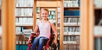 Composite image of girl sitting in wheelchair in school corridor