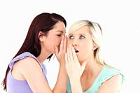 Portrait of a young woman telling her friend a secret