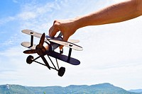 Close-up of  hand holding a model airplane against sky and mountain range.