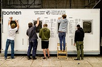 People removing a pricelist from the side of a portacabin at the end of a music festival (Ghent, Belgium). The sign reads ´Empty cup exchange´.