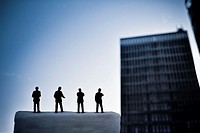 Silhouette of men in front of a blurred building. Symbolic business concept.
