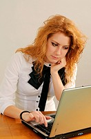 Redhaired young woman working with a computer.