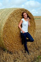 Young woman standing at a round bale of straw in Scania, Sweden.